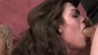 Naive looking slut deep throats 2 cocks